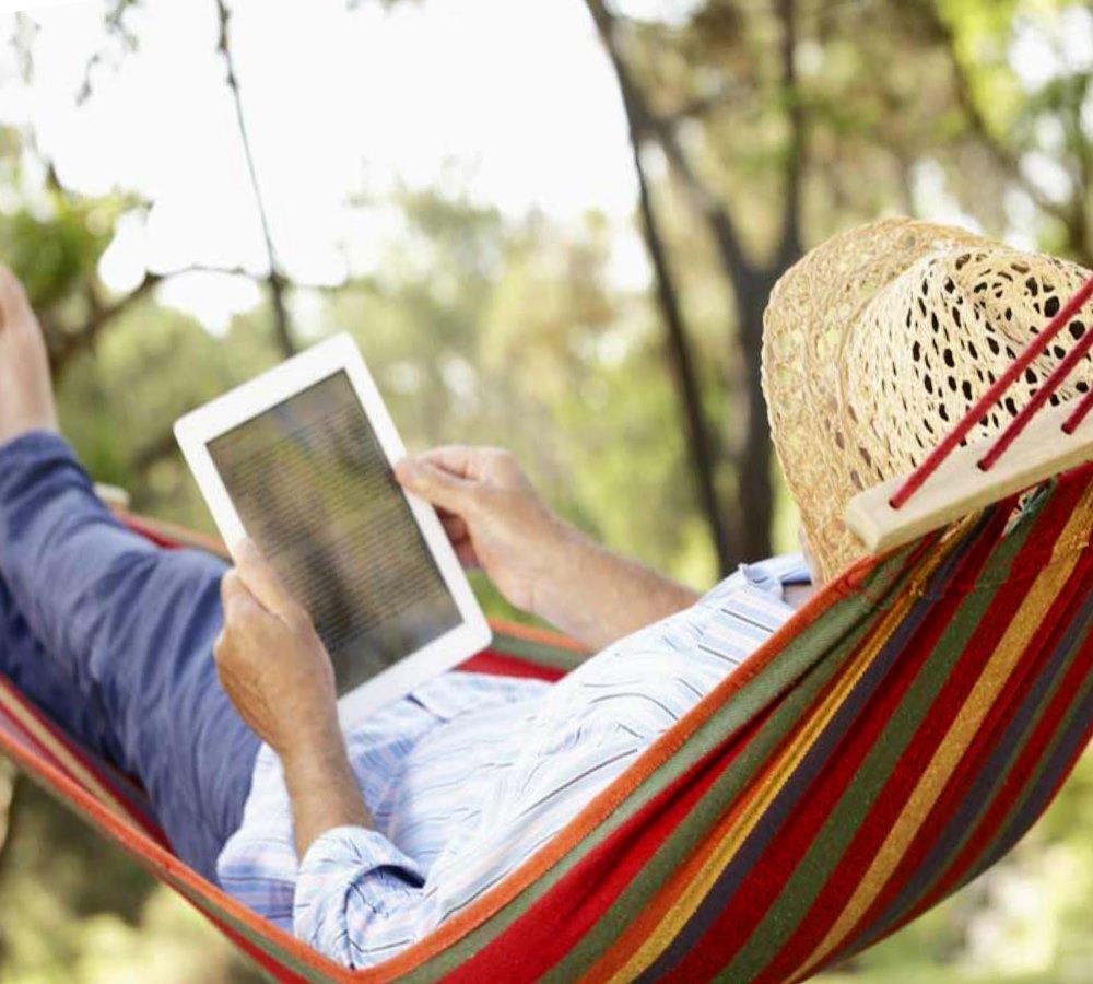Отдых на природе в гамаке с планшетом
