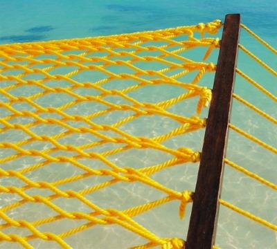Красивый сетчатый гамак желтого солнечного цвета на фоне лазурного моря