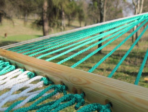 Бело-зеленый полосатый гамак из сетки висит в парке