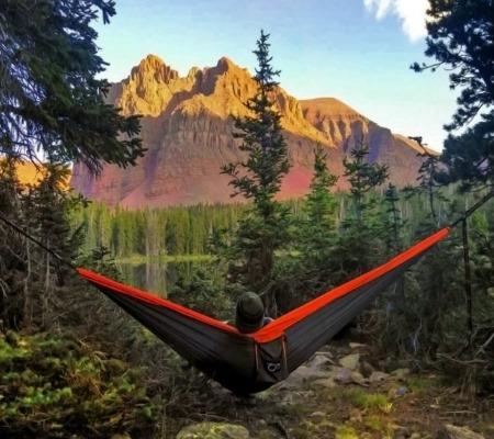 Человек отдыхает в горах с гамаком