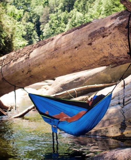 Девушка повесила гамак на поваленное дерево над горной речкой