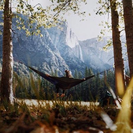 Мужчина в лесу спит в тентовом гамаке на фоне красивой природы