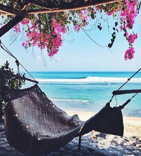 Веранда на пляже с гамаком внутри и розовыми цветами