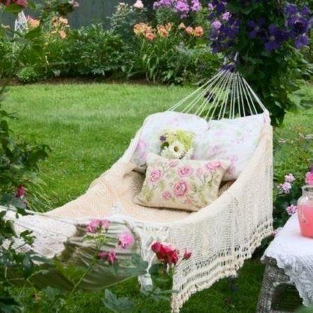 Садовый гамак на даче на фоне клумбы с цветами