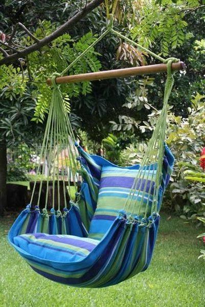 Полосатое подвесное кресло легко разместить на дереве в саду