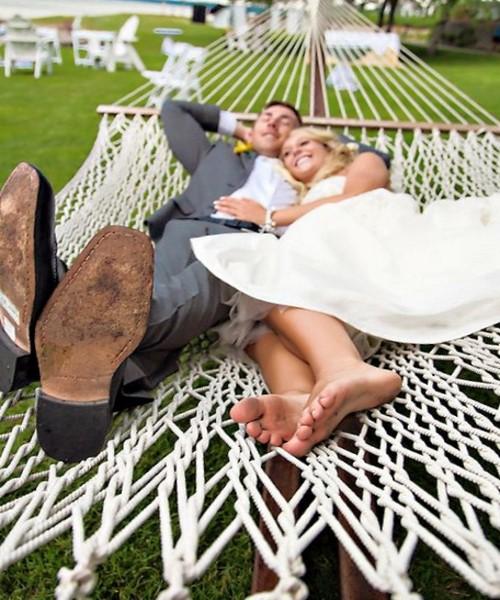 Жених и невеста отдыхают в белом гамаке сетке