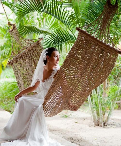 Невеста отдыхает в плетеном гамаке под пальмой