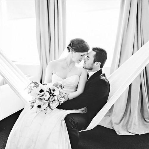 Влюбленные жених и невеста в гамаке на черно-белой фотографии